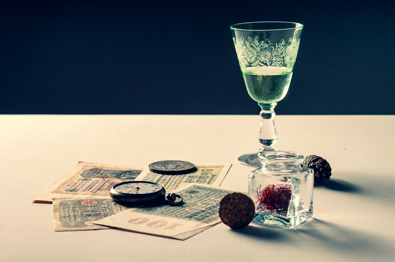 Stillleben mit Notgeld, Taschenuhr, Safran und Absinthglas