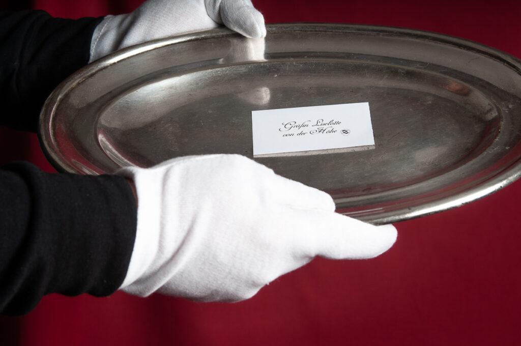 Visitenkarte auf Silbertablett wird mit weißen Handschuhen überreicht